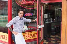 Portrait of male business owner opening diner door